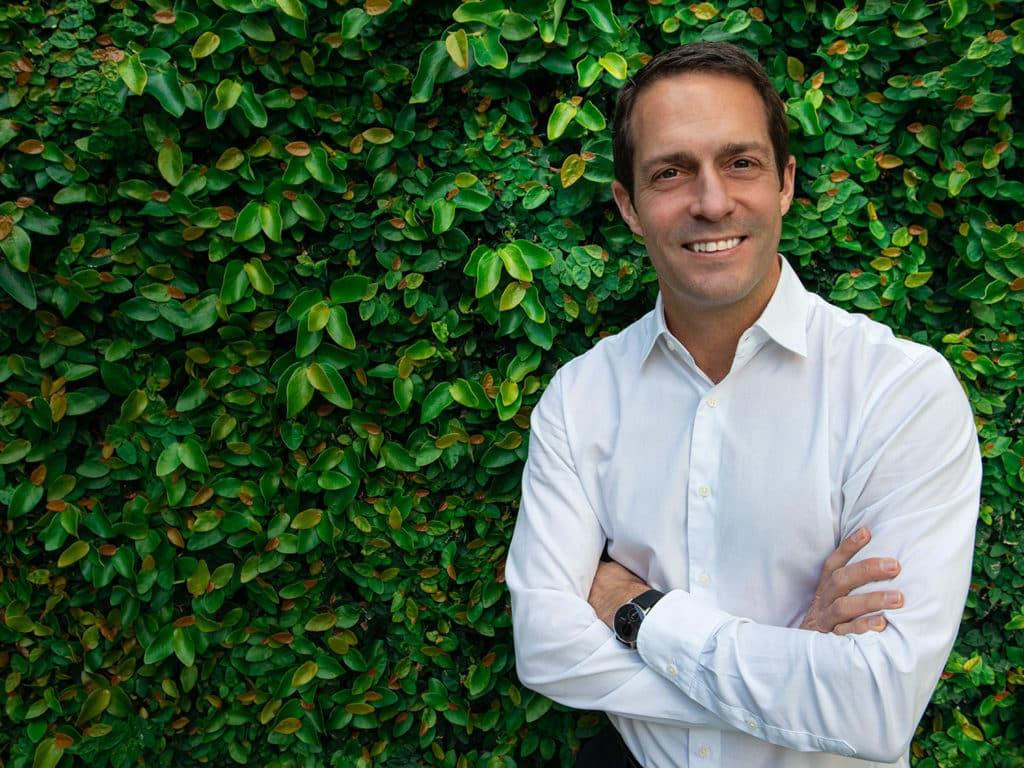 Nicholas Bruneau standing in front of a green vertical garden.